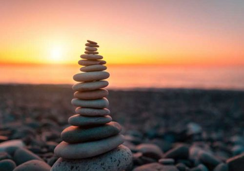 Stone pyramid on the background of sunset and sea on pebble beach symbolizing stability, zen, harmony and balance